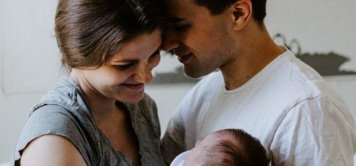 Una pareja feliz sonriendo a su hija.