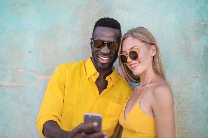 Piropos lindos y graciosos - Photo of smiling man in yellow shirt standing beside smiling woman in yellow spaghetti strap top looking at a phone