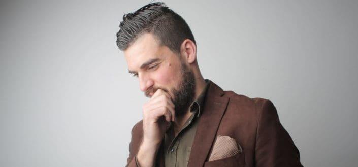 ¿Cómo Elegir Los Mejores piropos lindos? - Pensive man in brown coat holding his chin