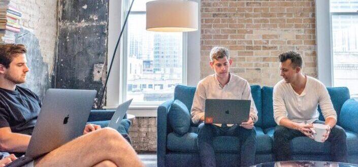 Tres hombres sentados en el sofá y sosteniendo una computadora portátil