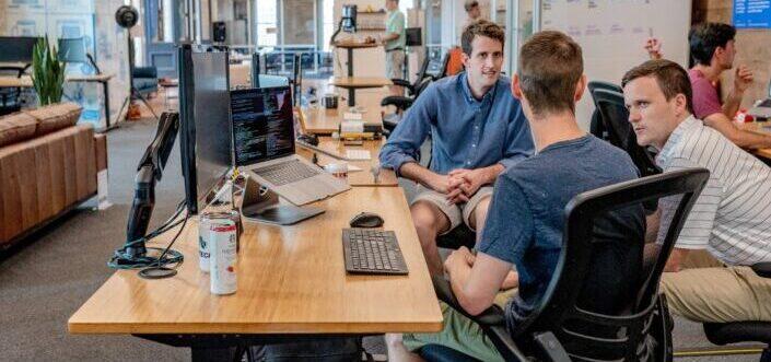 Tres hombres hablando frente a un monitor