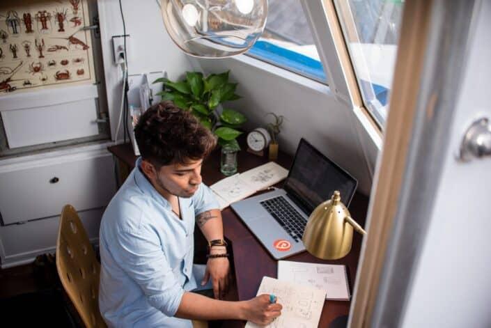 Hombre escribiendo en un cuaderno en su escritorio