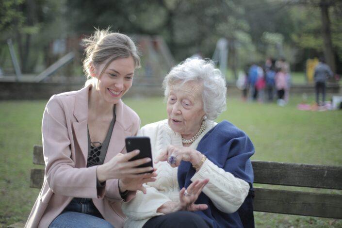 Mujer sosteniendo un teléfono a una mujer mayor