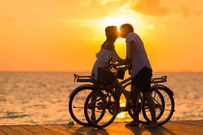 Pareja besándose al atardecer mientras sostiene sus bicicletas