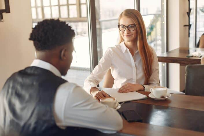 Mujer pelirroja entrevistando a un hombre