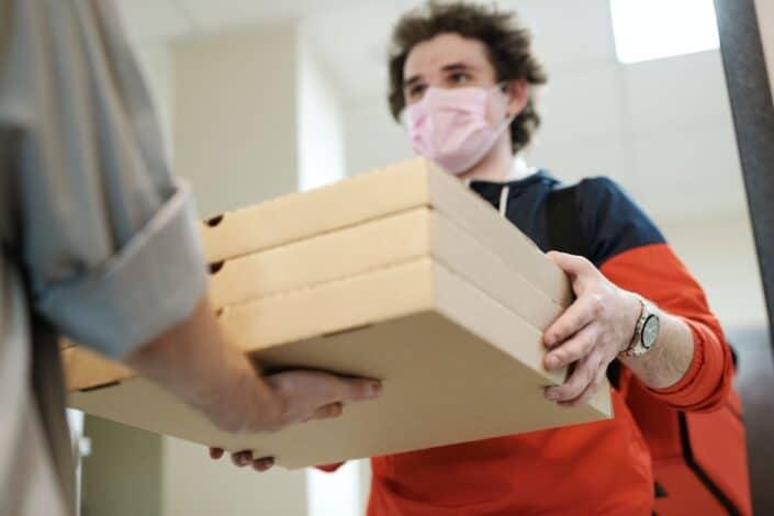 Chico entregando tres cajas de pizza a un cliente