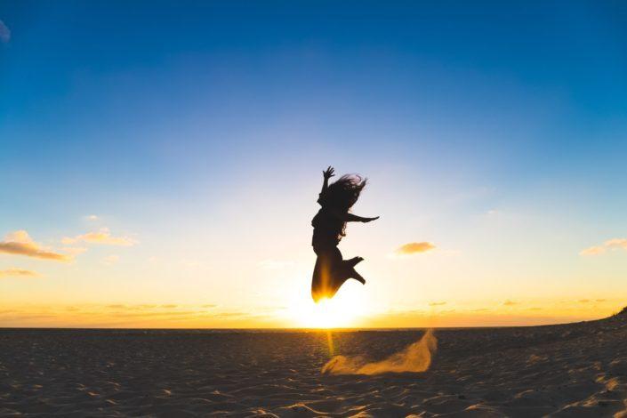 mujer saltando en la arena durante la puesta de sol
