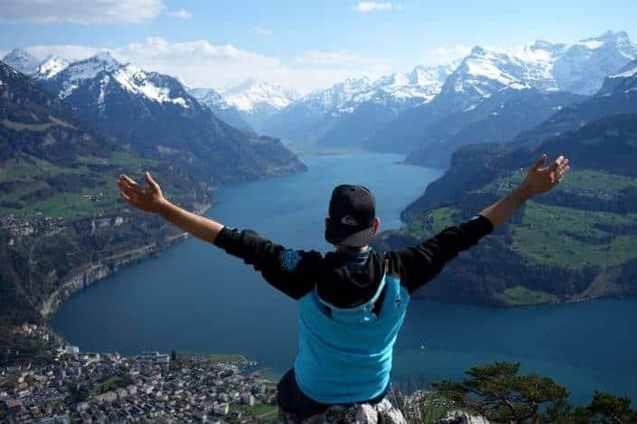 hombre en la cima de la montaña extendiendo sus brazos