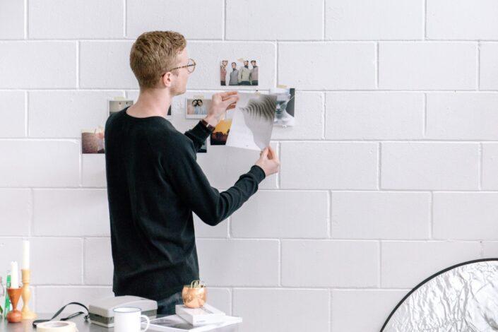 hombre que sostiene el papel delante de la pared