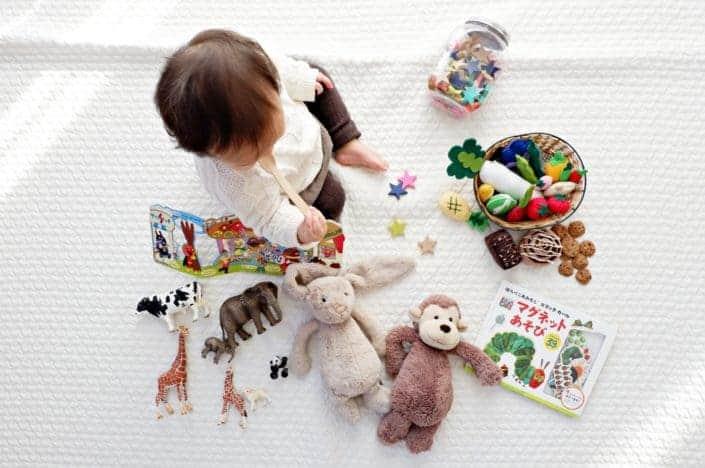 niño sentado mientras la tela rodeada de juguetes