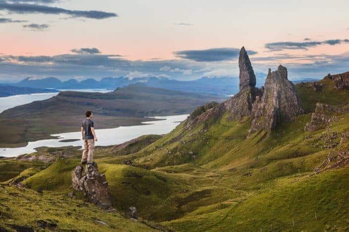 hombre de pie en la roca frente a la montaña