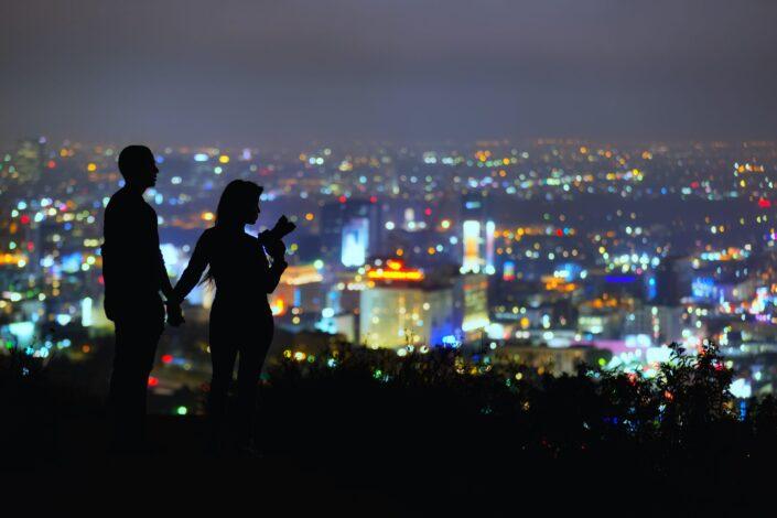 pareja de pie en la colina con vistas a la ciudad por la noche