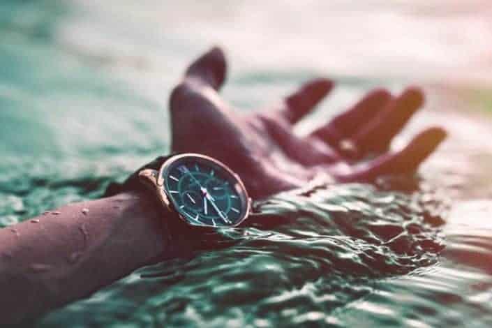 Foto recortada del brazo con reloj en el mar
