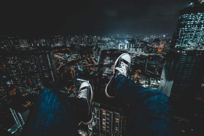 hombre en jeans frente al paisaje urbano por la noche