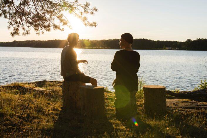 Dos amigos hablando frente al lago.
