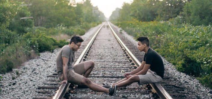 dos personas sentadas en los rieles del tren durante el día