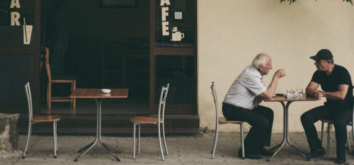 dos hombres charlando afuera de la cafetería