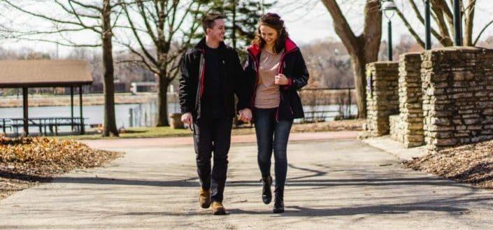 pareja tomados de la mano mientras camina en la calle