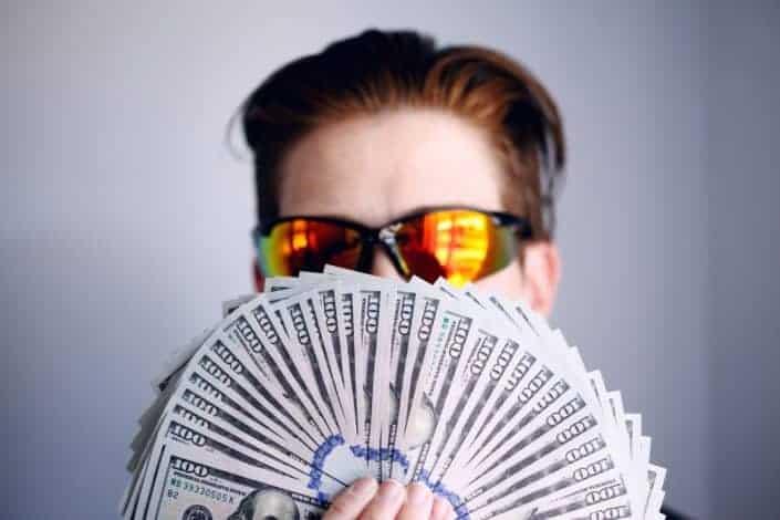 hombre con ventilador de billetes de cien dólares.