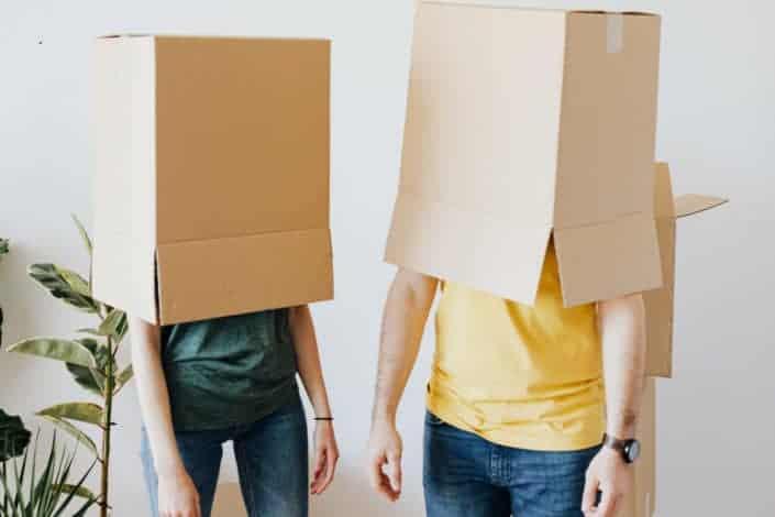 Pareja irreconocible llevando cajas de cartón en la cabeza.