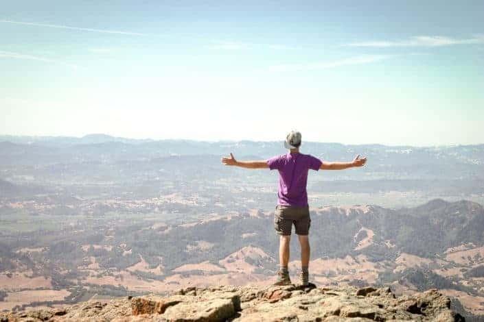 hombre de pie en la montaña marrón con los brazos abiertos