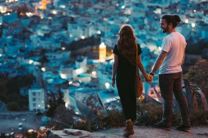 pareja tomados de la mano mientras ve la ciudad