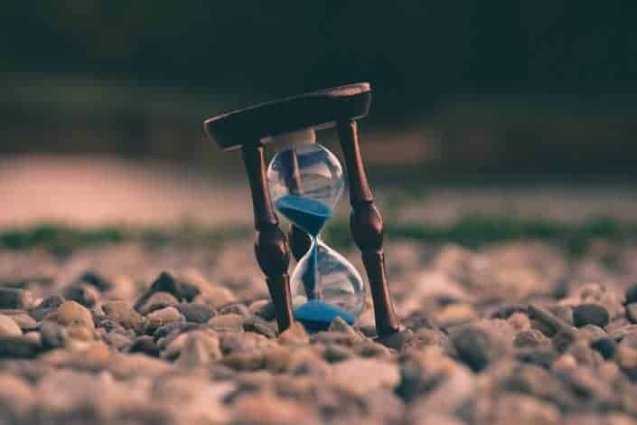 Fotografía de enfoque selectivo de reloj de arena azul sobre piedras