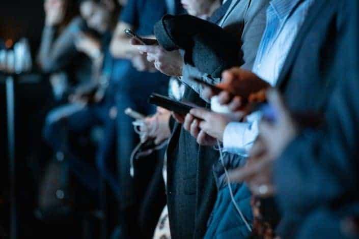 personas que usan el teléfono mientras están de pie