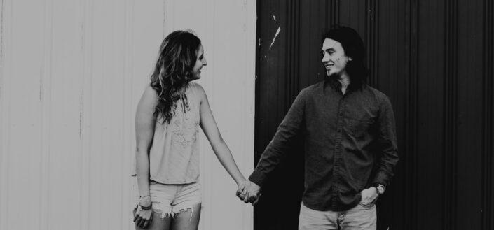 Fotografía en escala de grises de la pareja tomados de la mano