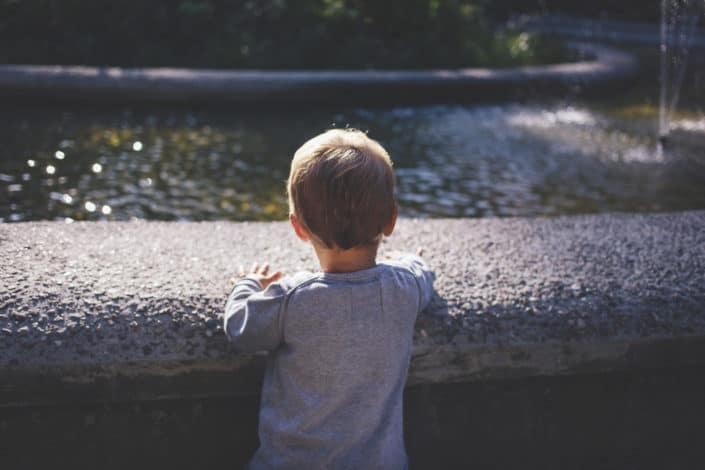 Niño jugando junto a la fuente