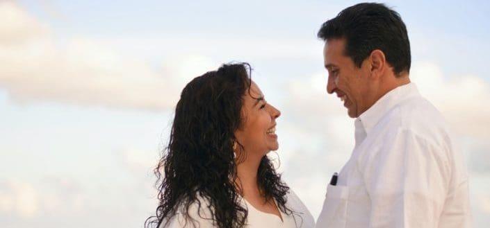 Pareja vestidos de blanco sonriendo el uno al otro