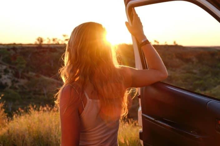 Chica mirando al sol fuera de su coche