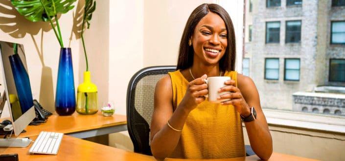 Chica tomando café en su oficina