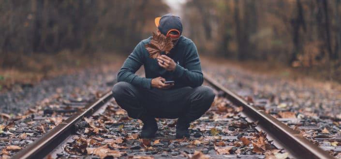 Guy cubriendo la cara con hojas en medio de las vías del tren