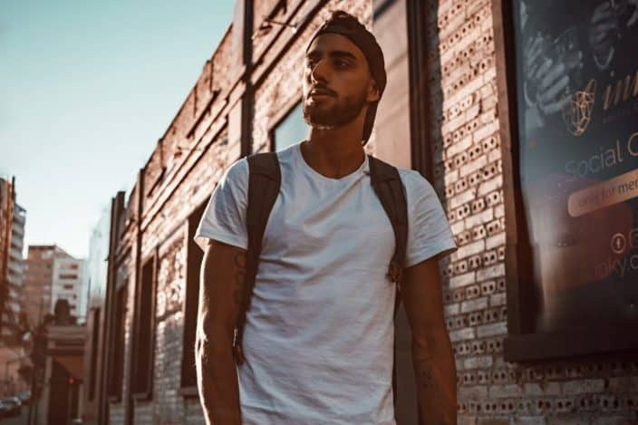 Chico caminando con una mochila en la calle