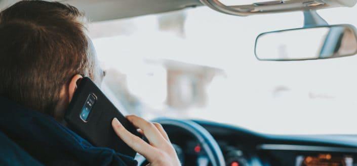Chico haciendo una llamada mientras conduce