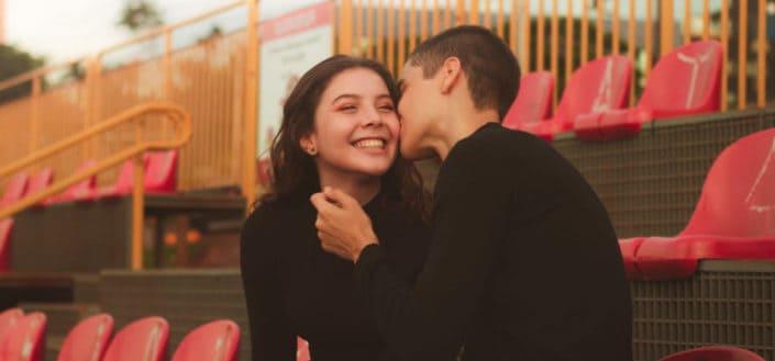 Chico besando la mejilla de una chica