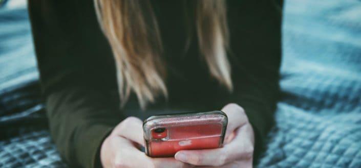 Chica en la cama leyendo un texto en el teléfono