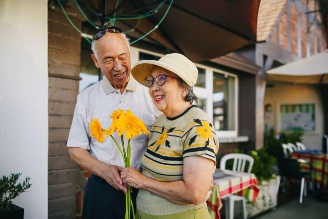 Una pareja de ancianos sonriendo mientras sostiene la flor - regalos para mamá