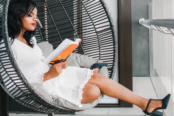 Niña sentada en una mecedora y leyendo un libro