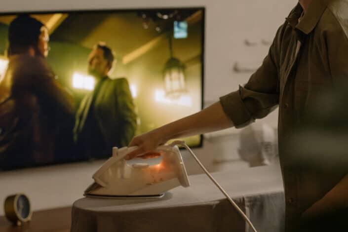 Mujer planchando ropa mientras ve la televisión