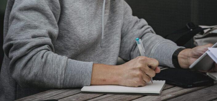 hombre escribiendo algo en su cuaderno