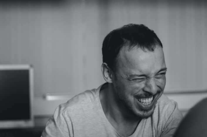 Guy sonriendo mientras entrecierra los ojos