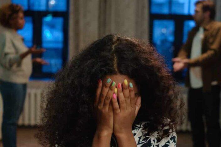 Chica cubriendo su rostro con sus manos
