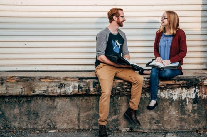 Chico y chica sentados en una repisa hablando con un libro abierto en sus regazos