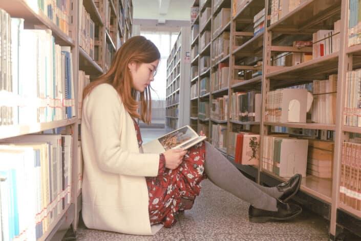Niña leyendo un libro en el piso de una biblioteca
