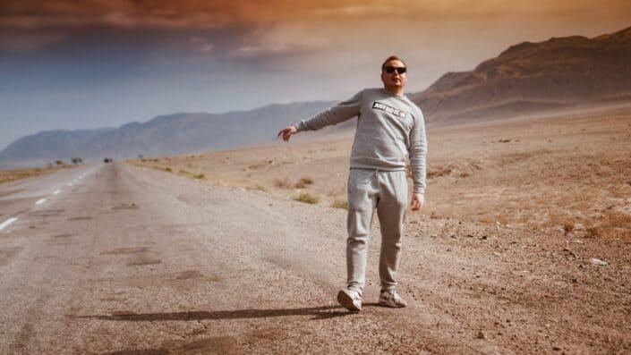 Chico apuntando a una carretera del desierto