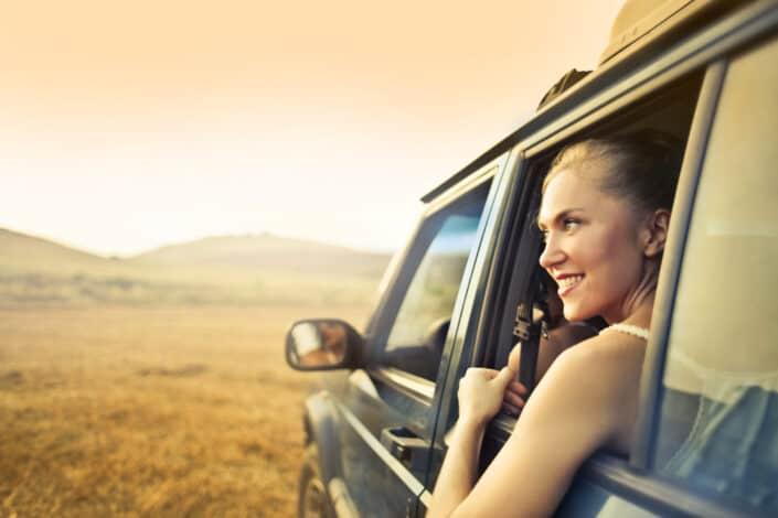 Chica mirando fuera de una ventana de coche abierta