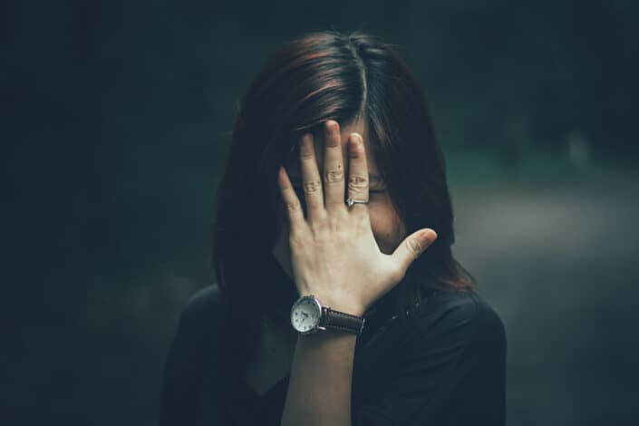 Chica cubriendo su rostro con su mano izquierda