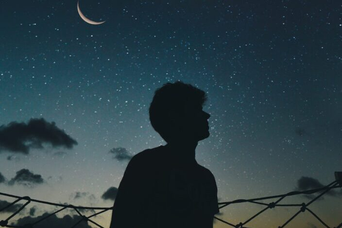 silueta de un hombre mirando un cielo estrellado